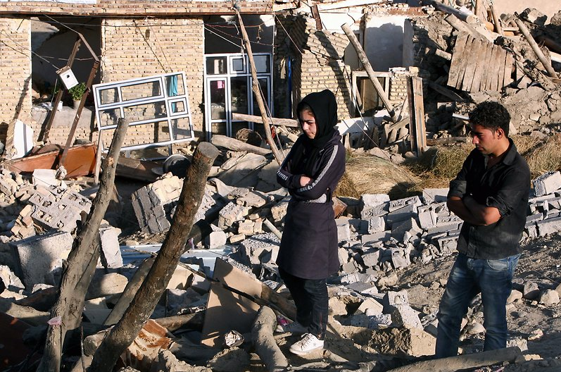 """A brother and sister stand amidst the rubble of their house in the village of Bajeh Baj, in the city of Varzaqan (Credit: EPA)"""